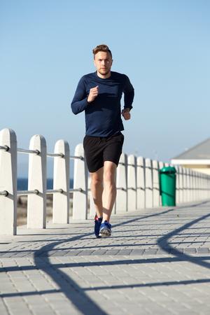 Ganzkörperporträt des aktiven jungen Mannes, der draußen läuft
