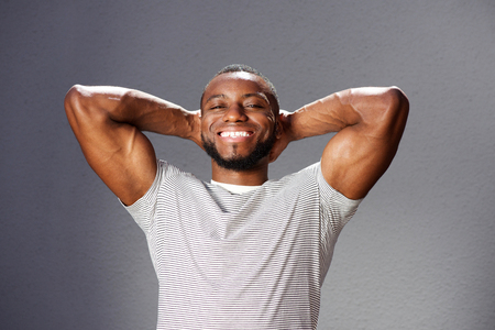 black male: Close up portrait of handsome muscular man smiling with hands behind head