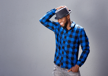 enjoy space: Portrait of happy handsome man laughing with hand to hat Stock Photo