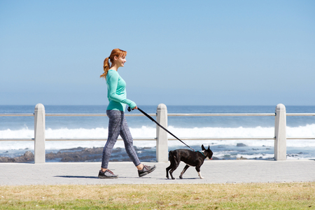 Full body portrait of fit woman smiling and walking dog on path by sea