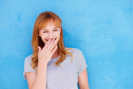 Close up portrait of happy woman standing with hand to mouth laughing Stock Photo