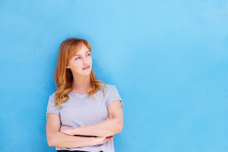 Portrait of thinking woman standing with arms crossed by blue wall