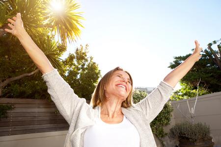 Gelukkig portret van glimlachende oudere vrouw met uitgestrekte armen Stockfoto