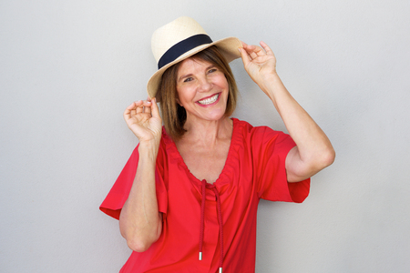 Portrait of older woman smiling with hat against gray wall