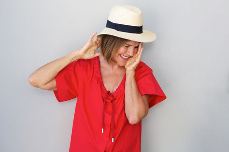 Portrait of older woman laughing with hat against gray wall Stock Photo