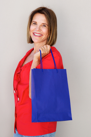 Side portrait of happy older woman with blue shopping bag Banco de Imagens