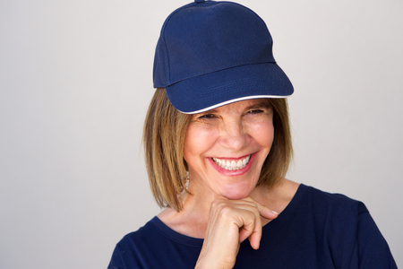 50 to 60: Portrait of fun older woman laughing with blue cap