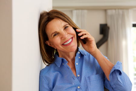 Portrait of middle age woman leaning against wall and talking on mobile phone