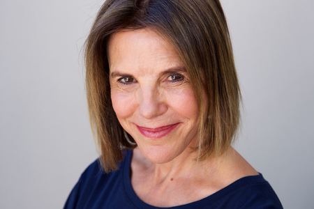 senior woman: Close up portrait of mature woman smiling against gray wall