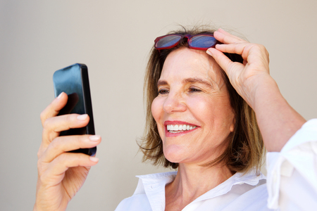 メガネを押しながら携帯電話を見て、ビジネスの女性の肖像画を間近します。 写真素材