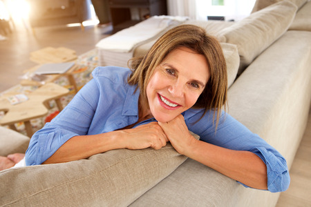 Portrait of happy older woman relaxing at home on couch Stock Photo