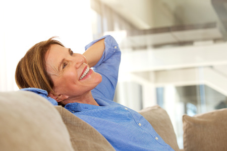 Portrait of older woman smiling and relaxing at home Stock Photo
