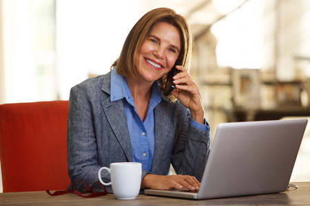 Portrait of smiling business woman sitting at desk with phone and laptop