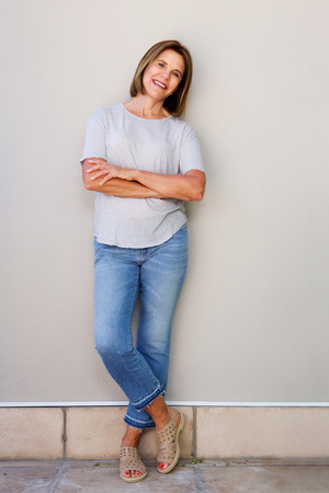 Full body portrait of attractive senior woman smiling with arms crossed Stock Photo