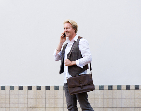 background person: Side portrait of business man walking and talking on cellphone Stock Photo