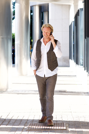 white person: Full length portrait of mature man walking around the city and talking on the mobile phone Stock Photo