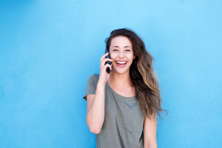 Front portrait of young laughing woman talking on cellphone against blue background