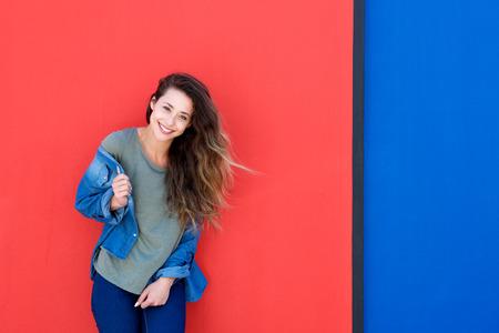 mujer alegre: Retrato de joven mujer feliz de pie contra el fondo azul y rojo
