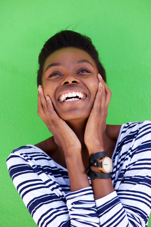 laughing face: Portrait of young woman laughing with hands on face