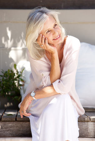 笑みを浮かべて、外のポーチに座っている年配の女性の肖像画