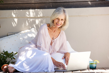 Full body portrait of smiling older woman sitting outside with laptop Stock Photo