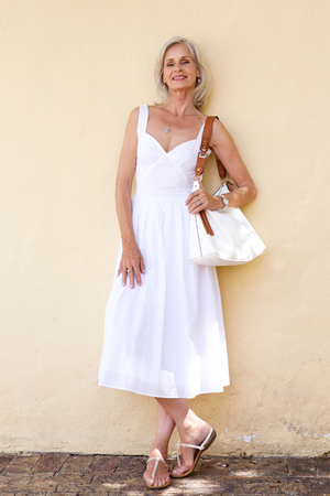 Full body portret van gelukkige oudere vrouw in lente jurk staande met portemonnee Stockfoto