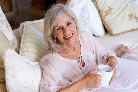 Close up portrait of smiling older woman sitting on couch drinking coffee