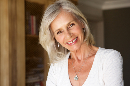 Close up portrait of beautiful older woman standing in study smiling Stockfoto