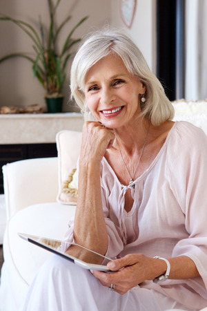 Portrait of smiling older woman in living room with tablet