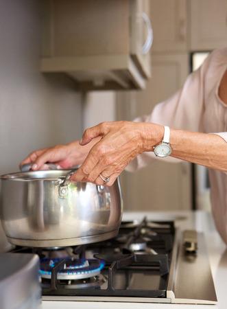 ストーブの上に鍋に水を沸騰、年上の女性の肖像画を間近します。
