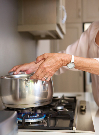 오래 된 여자 끓는 물 냄비에 난로 위에 초상화를 닫습니다