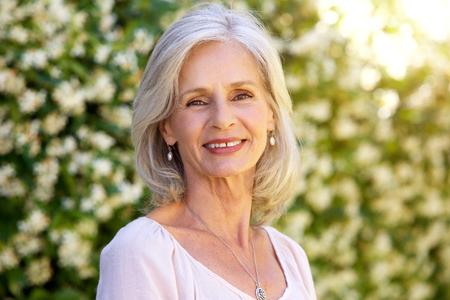 Close-up portret van gelukkige oudere vrouw die buiten in de zomer staat