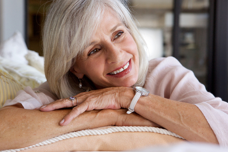 50 to 60: Close up portrait of comfortable older woman sitting on couch relaxed Stock Photo