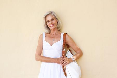 Retrato de feliz mujer mayor de pie en vestido blanco con monedero Foto de archivo - 74022003