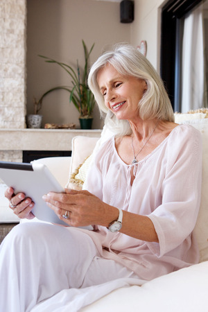 50 to 60: Portrait of older woman smiling sitting on couch with tablet