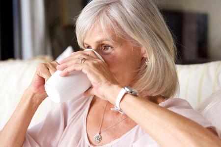 mujeres ancianas: Cerca de retrato de la mujer más vieja del té para beber en el sofá en el interior Foto de archivo