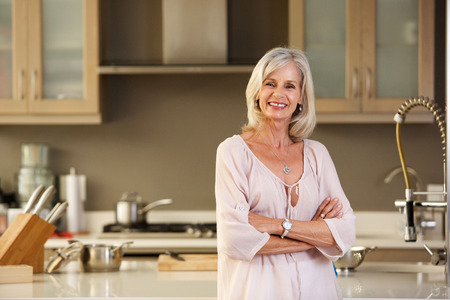 Portrait of smiling older woman standing in modern kitchen Stock Photo