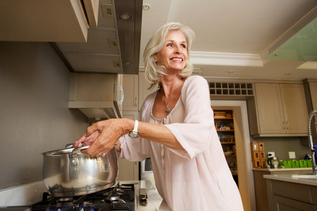 Ritratto di vecchia donna sorridente acqua bollente sul piano cottura della cucina