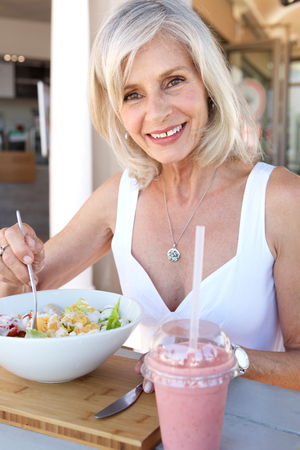 Close up portrait of healthy older woman eating at outdoor restaurant Stock Photo