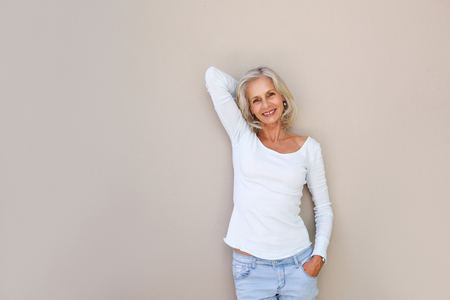 Portrait of happy carefree older woman with hand by head Imagens
