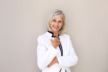 Portret van het mooie oudere vrouw glimlachen en status door muur Stockfoto