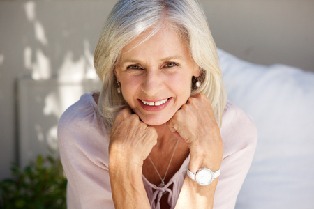 Close up portrait of smiling older woman with hand in hands outside