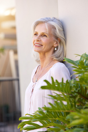 50 60 years: Portrait of older woman leaning on wall outside smiling