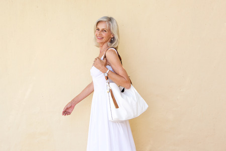 50 to 60 years: Portrait of happy older woman in summer dress walking with purse
