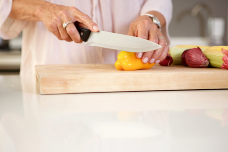 Close up portrait of older woman cutting fresh vegetables in kitchen Stock Photo