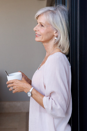 Close up portrait of smiling older woman standing in home drinking coffee