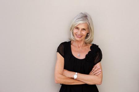 Portret van lachende oudere vrouw leunend op de muur met de armen gekruist Stockfoto