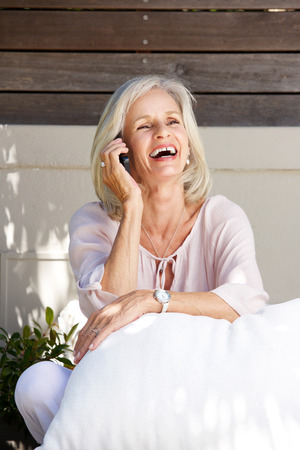 telephone call: Portrait of beautiful older woman laughing on telephone call outside Stock Photo