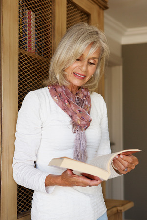 50 to 60: Portrait of beautiful older woman in study reading book