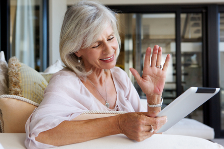 mujeres ancianas: Close up portrait of happy older woman at home with touch screen tablet Foto de archivo